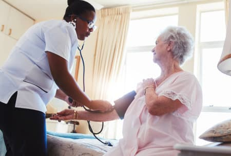 nurse checking the blood pressure of an old woman