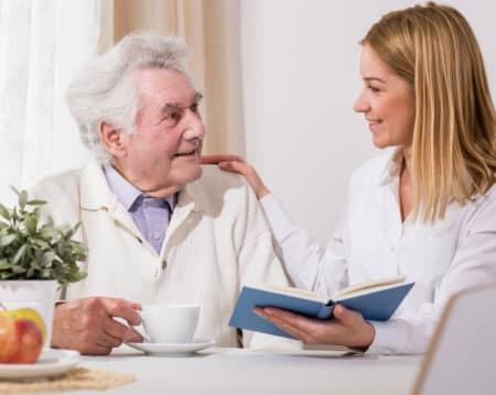 old man reading books with her caregiver