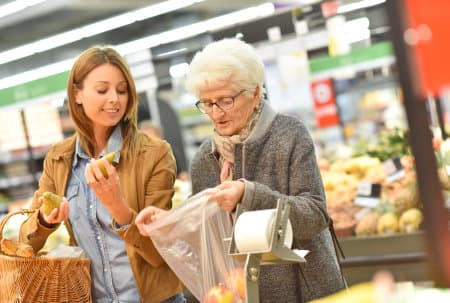 old woman and caregiver doing grocery shopping