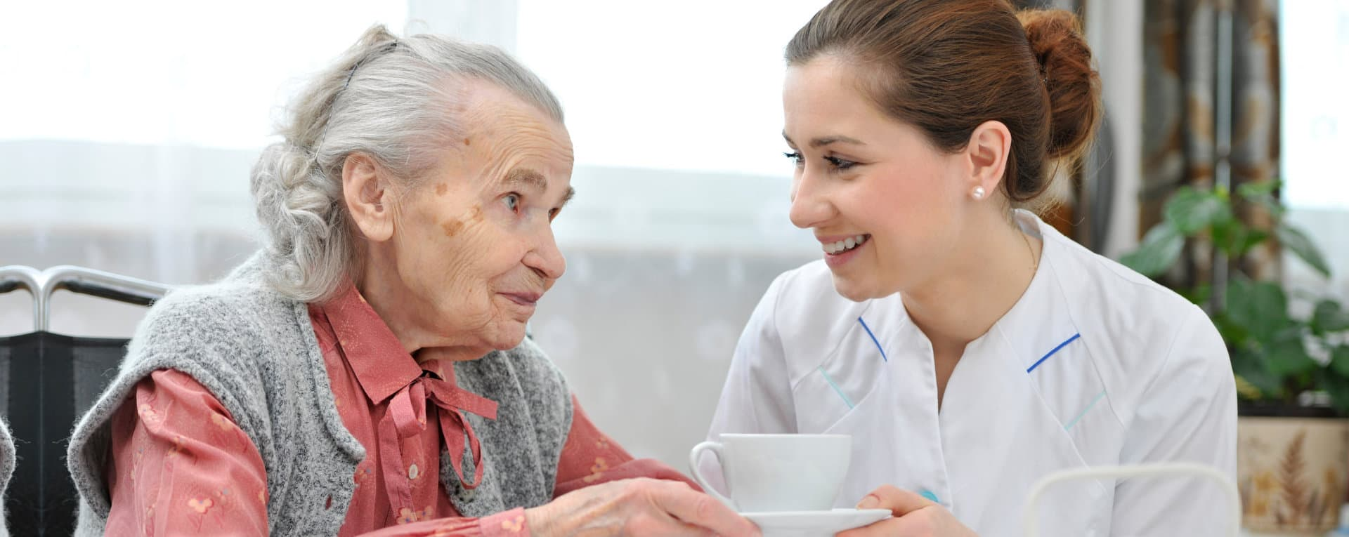 caregiver serving coffee to an old woman